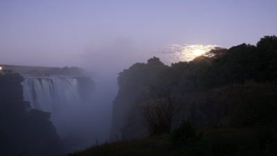 Medium wide angle top of falls as night falls and moon rises behind moody clouds which sweep towards camera as gets darker
