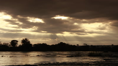 Medium wide angle Zambezi River above Falls looking across water to silhouetted tree lined river bank with god rays through stormy evening clouds