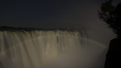 Medium wide angle looking diagonally across face of motion blurred Falls at night with spectacular lunar rainbow