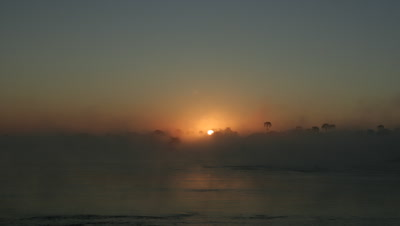 Wide angle sunrise over misty Zambezi river from darkness to full sun with fast flowing river