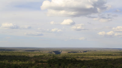 Wide angle looking across top of Batoka Gorge from high point revealing gash in landscape and distant horizon, clouds scud to camera