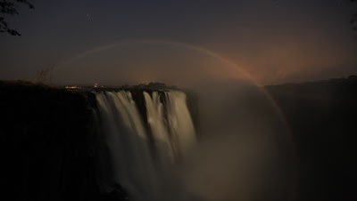 Medium wide angle view across face of motion blur water Falls at night with full lunar rainbow circling Falls then fades as day dawns and burns out sky