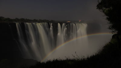 Medium wide angle beautiful lunar rainbow rises across motion blurred Falls at night framed by dark gorge with starry sky