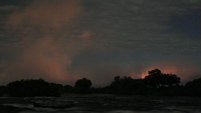 Mid shot looking across dark Zambezi River to dramatic orange spray rising at top of falls at night