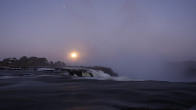 Medium wide angle looking across water flowing over edge of falls as moon rises behind spray cloud it glows eerily becoming moody, dark and dramatic