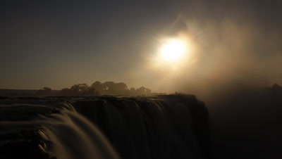 Mid shot looking across water flowing over edge of Falls to rising moon which becomes misty and dramatic as spray cloud rises