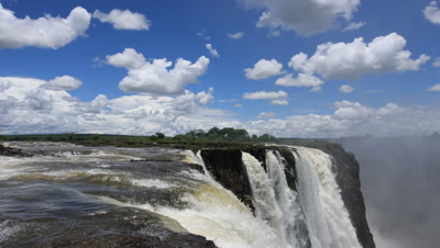 Mid shot looking across water flowing over edge of Falls with rising spray, blue sky and boiling fluffy white clouds