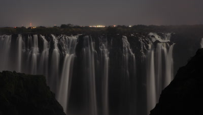 Medium wide angle looking straight across at face of Falls with motion blur multiple single falls - dry season - with lights of Livingstone town