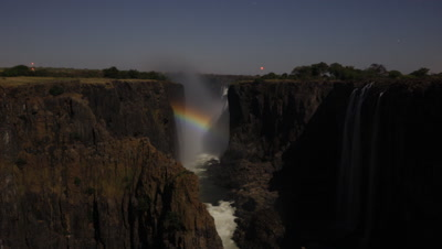 Medium wide angle looking upstream through and along gorge to face of Falls in moonlight with small lunar rainbow