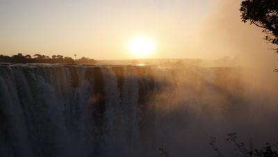 Mid shot looking straight across at Falls into sun with golden early morning light illuminating rising spray