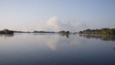 Wide angle looking across calm river to rising spray of Falls on horizon with clear blue sky