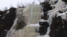 Small Evergreen Locked Into Frozen Waterfall On Cliff Along Lake Superior North Shore