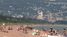 People Sunning, Enjoying The Beach, Water, On Lake Superior, Duluth In Bg