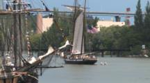 Tall Masted Sailing Ship, Motoring Past Anchored Ships In Harbor